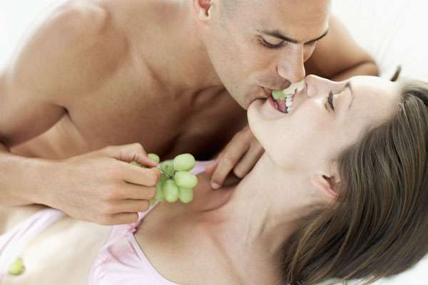 pareja juego erótico con uvas